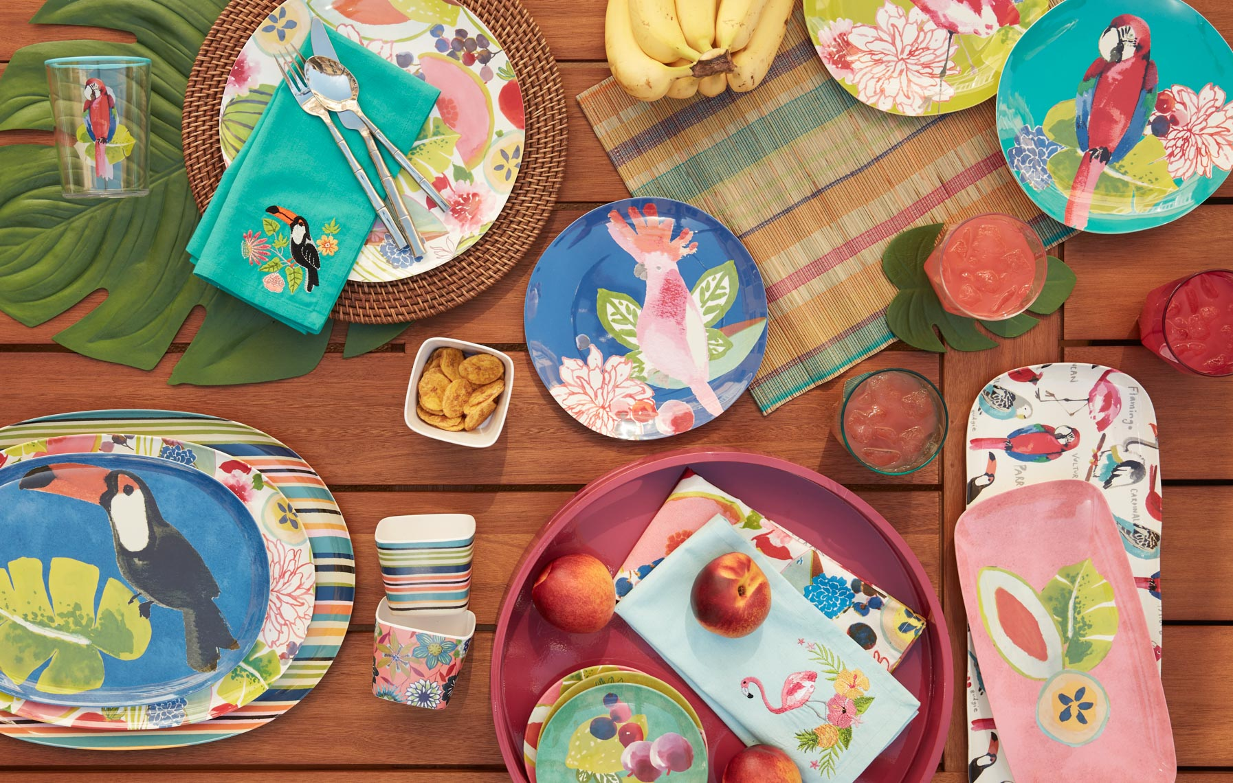 Colorful Plasitic dinnerware with fruit and placemats and artichokes on teak table
