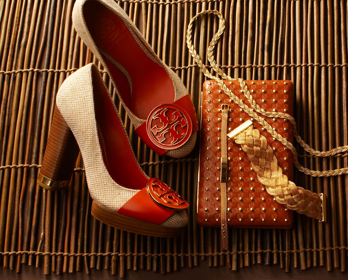 red and tan shoes with wooden heels next to brown handbag and jewelry