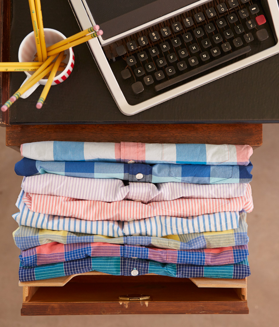 drawer full of folded plaid summer shirts next to desk with laptop and pencils