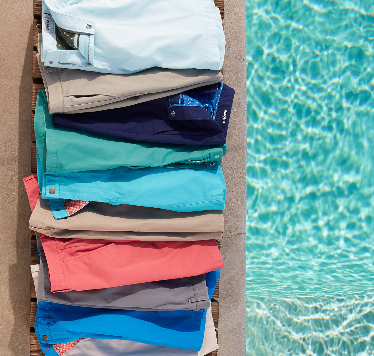downward view of selection of colorful shorts folded on cement next to pool
