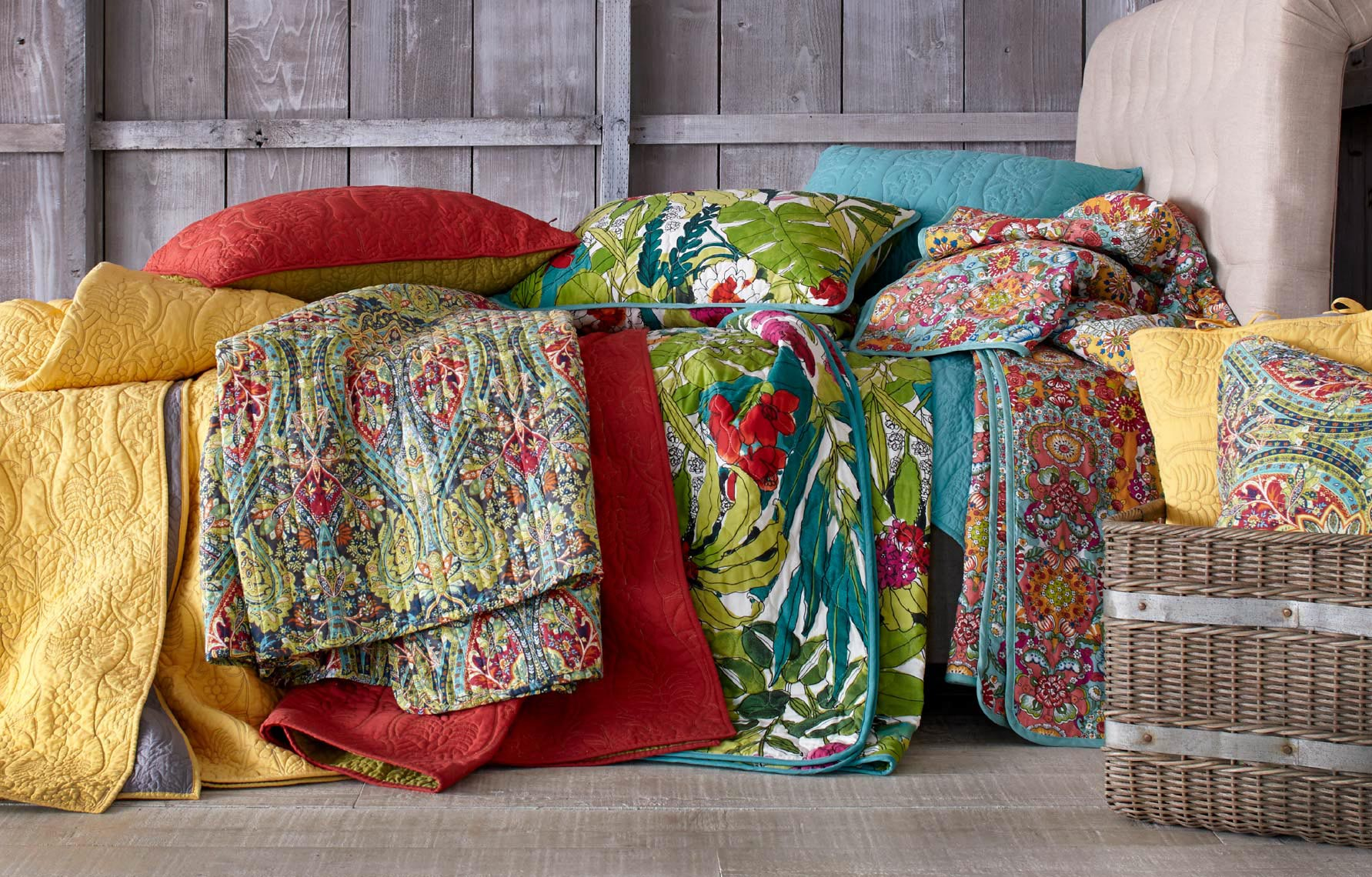 bed with colorful array of patterned quilts with wooden barn door