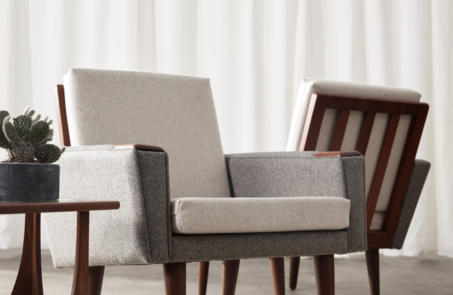 2 grey fabric armchairs with wooden legs