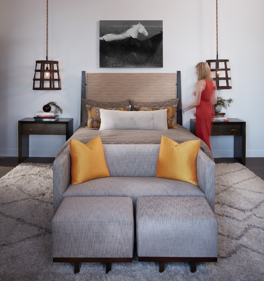 bedroom interior with grey couch with orange pillows and bed on grey patterned rug San Francisco interior photographer