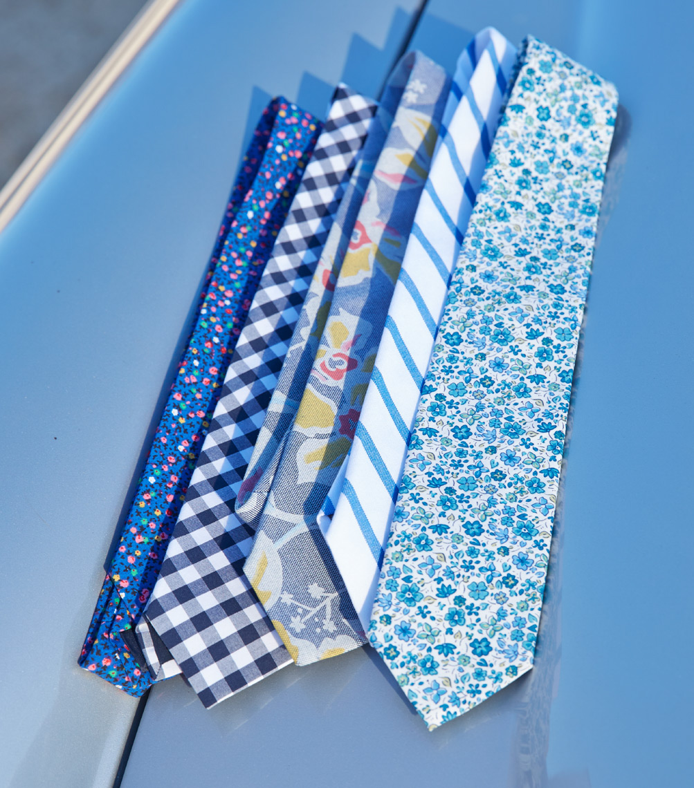 folded blue and white patterned ties sitting on hood of blue car