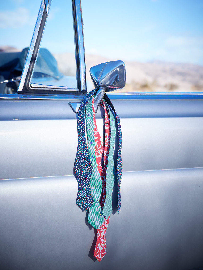 colorful patterned ties hanging from silver car mirror