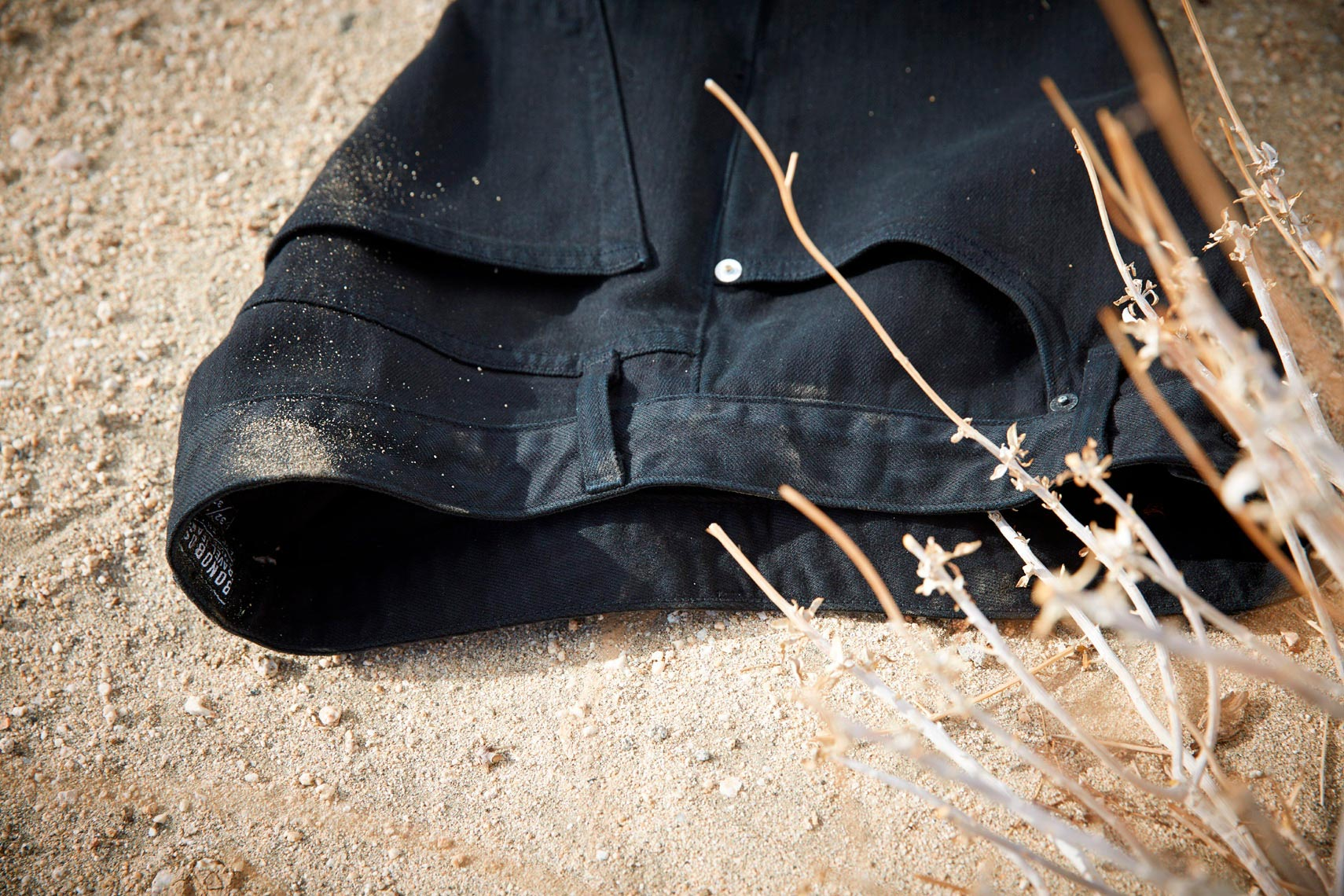 pair of black dress pants on sandy desert floor