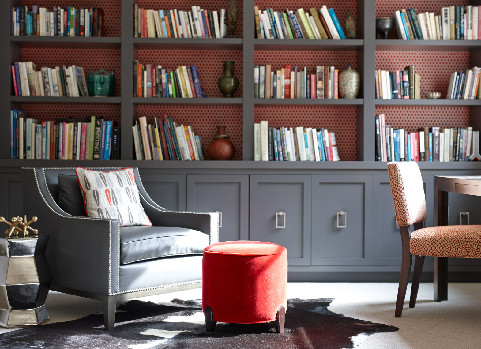 home library interior with chic grey bookshelves, grey armchair and red ottoman