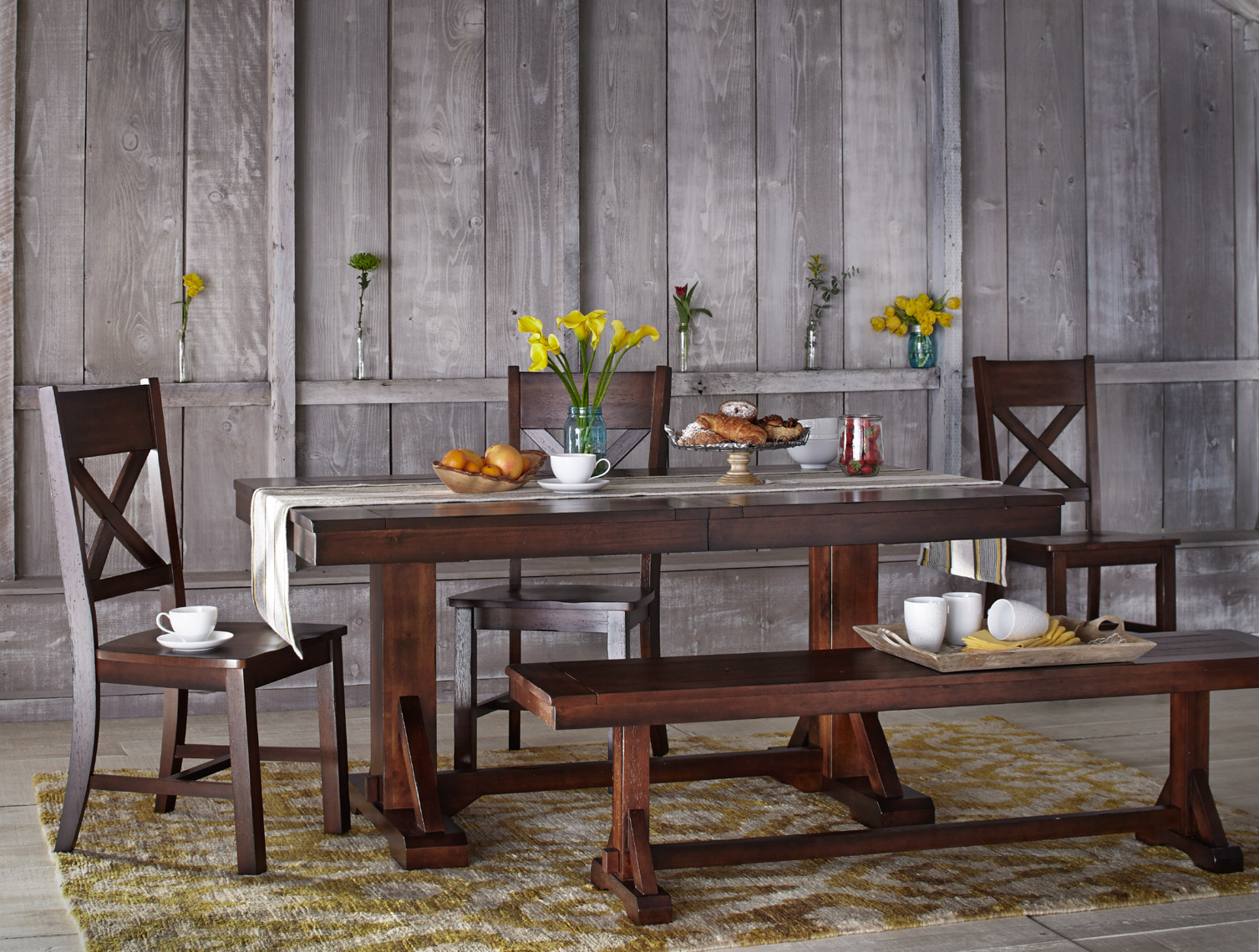 wooden dining table setup and flower decorations on barn door
