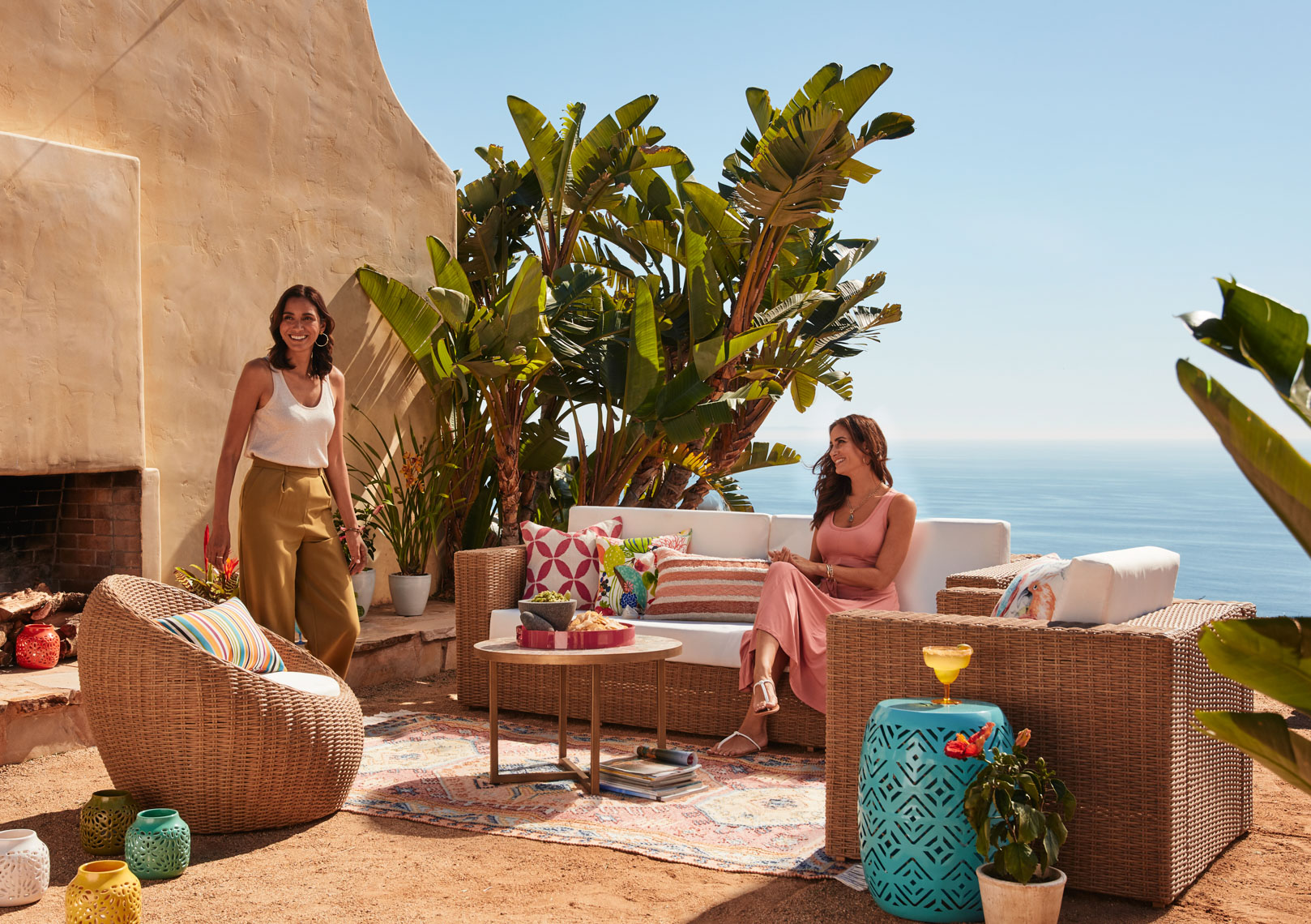 Two women at outdoor seating with wicker furniture and white cushions and rug in the sun overlooking the ocean