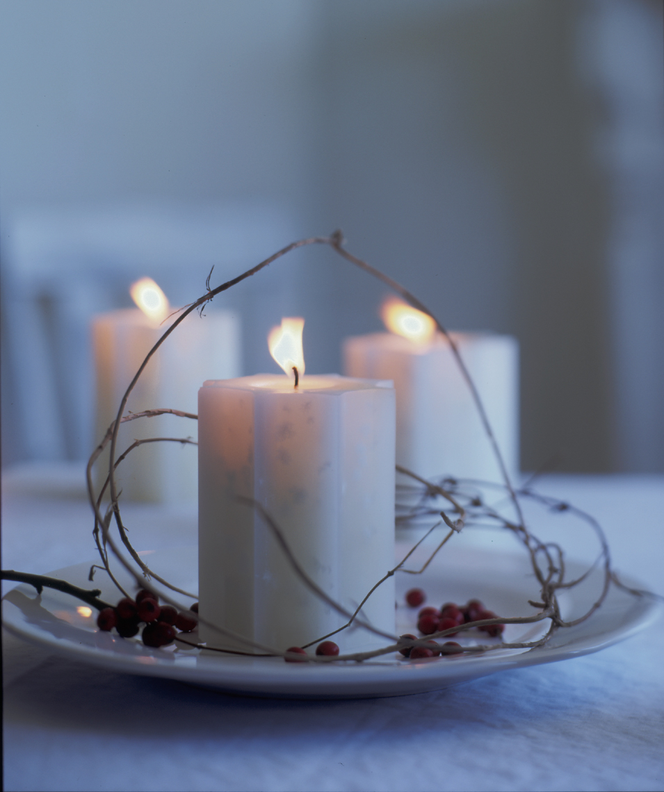 3 white lit candles wrapped in twine on white plate with twig and berries