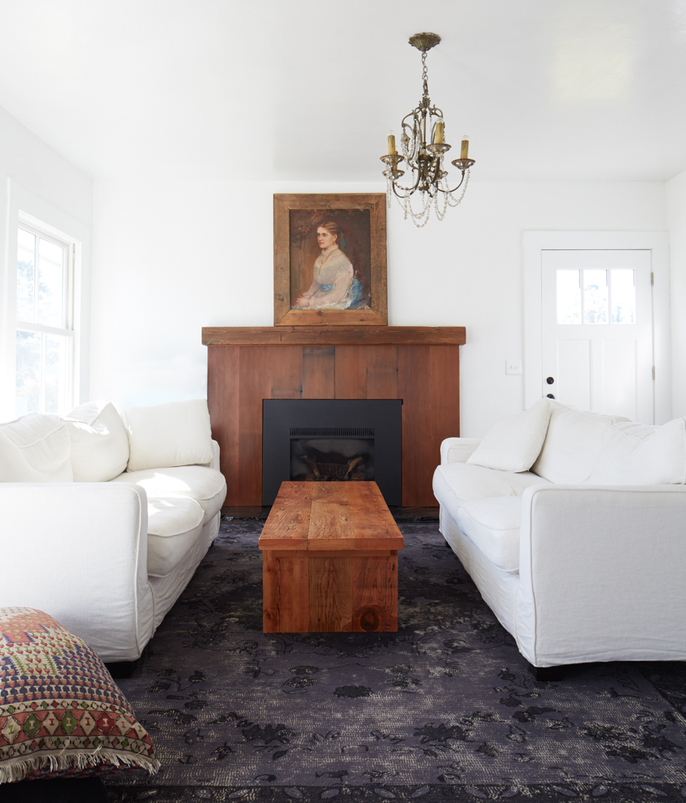 living room interior with white couches and wooden block table on grey carpet with wooden fireplace