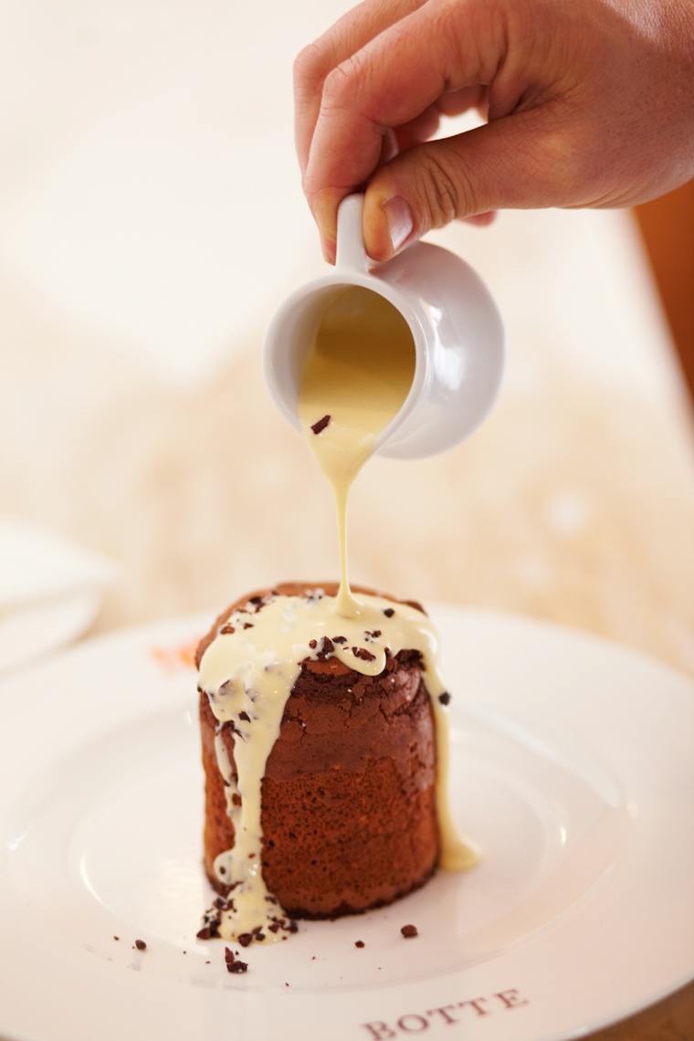 drizzling creme anglaise on a chocolate torte San Francisco food photographer