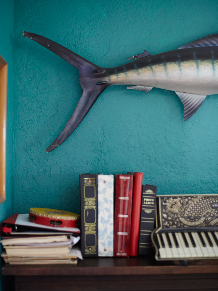 bedroom interior with blue wall and fish sculpture and stacks of books on a shelf