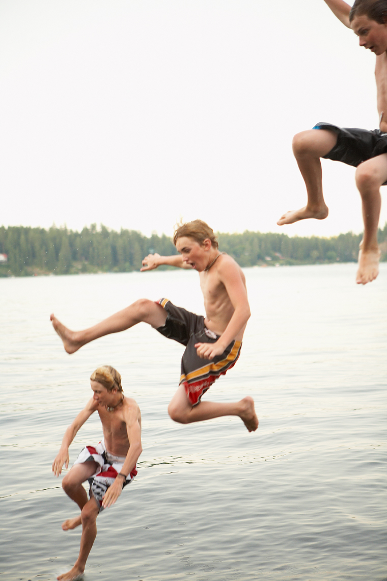Three boys in bathing suits leap playfully off a roof into a calm lake