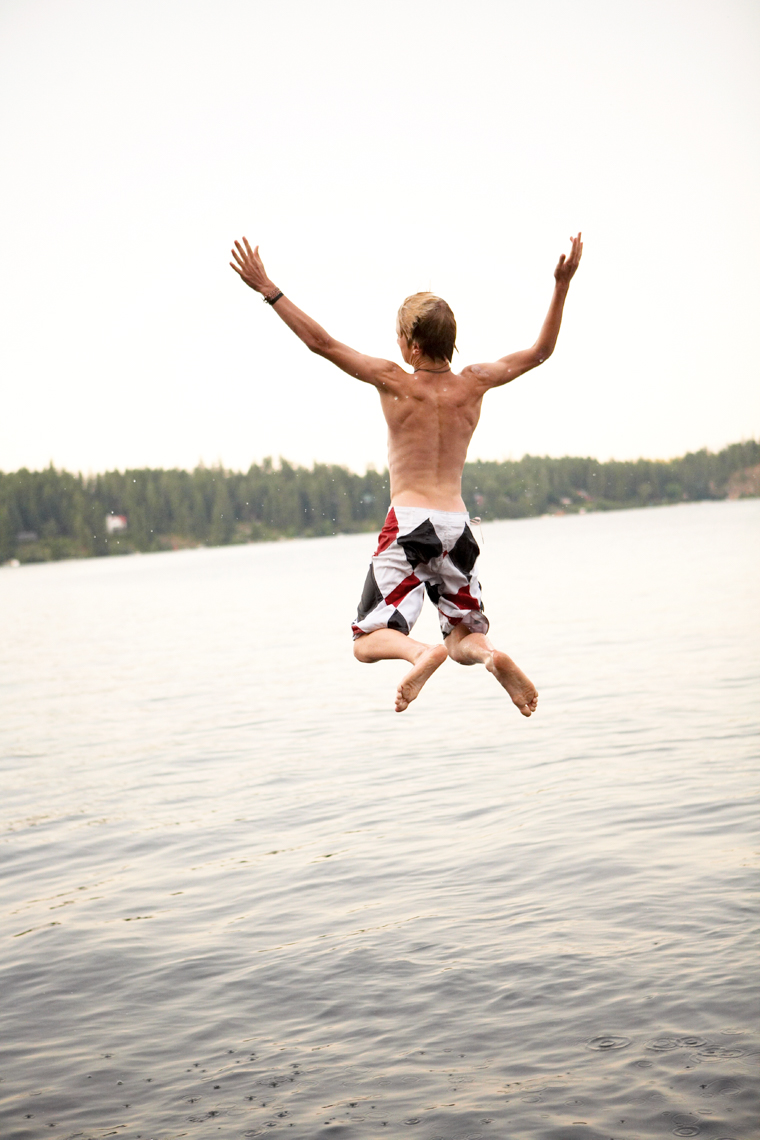 Boy in bathing suit seen joyfully leaping into a lake from behind