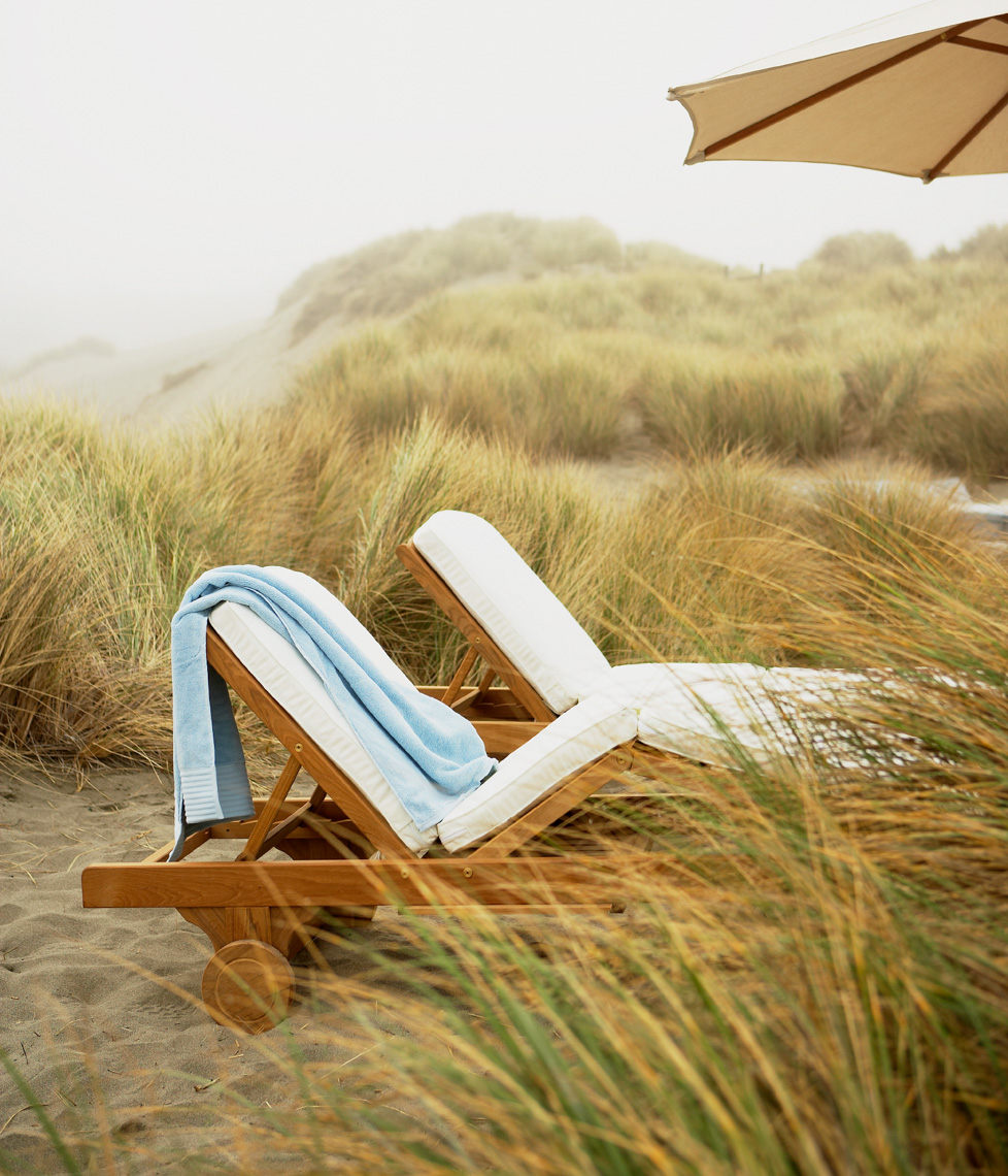 blue beach towel draped over teak wooden chaise with white cushion on sandy beach San Francisco lifestyle photographer