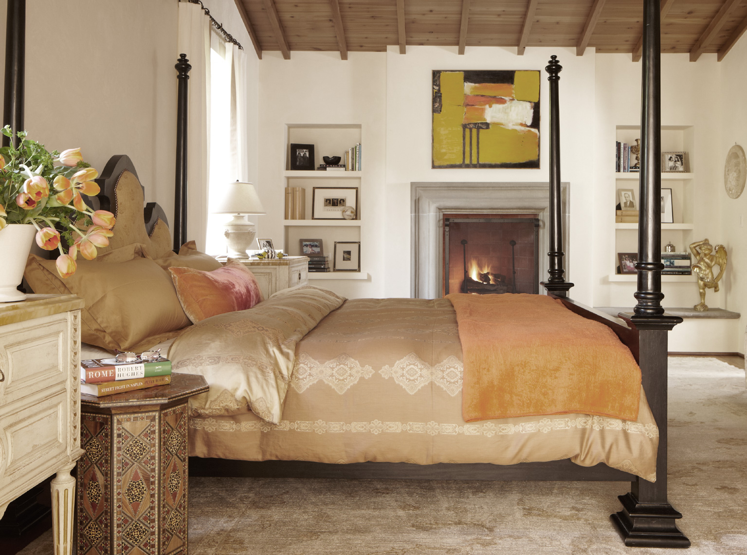 bedroom with black bed frame and golden bedding and fireplace