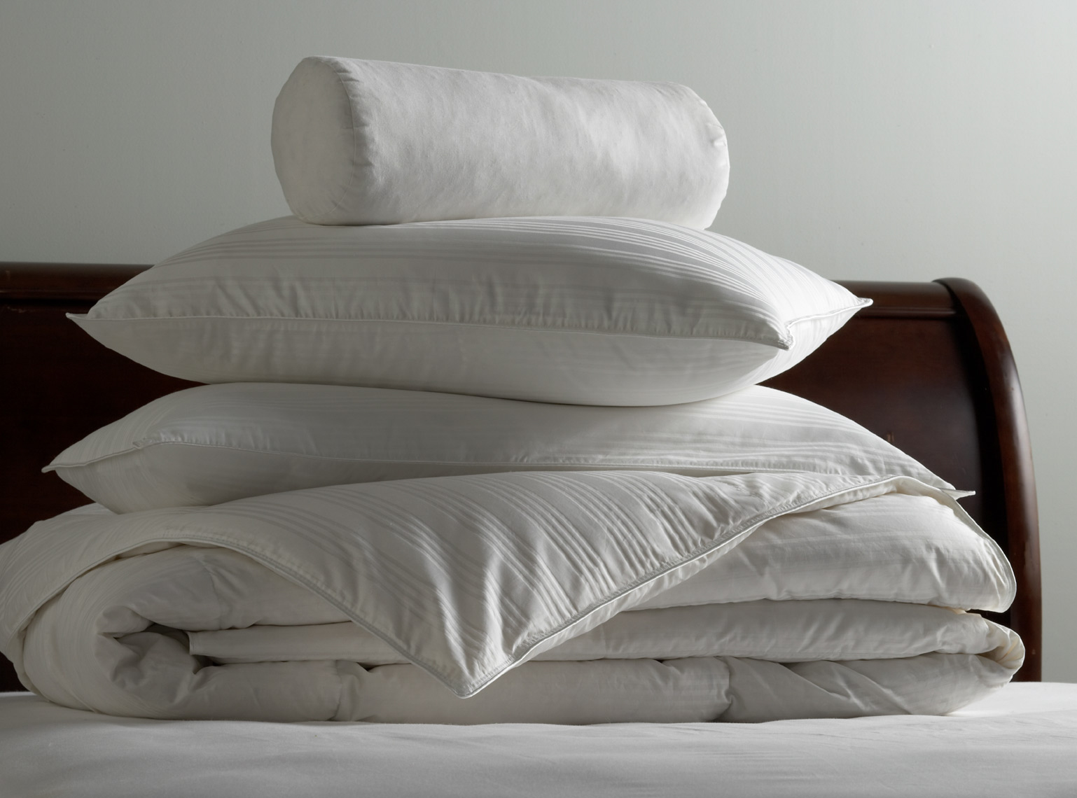 stack of white bedding on white bed with brown-stained wooden headboard San Francisco product photographer