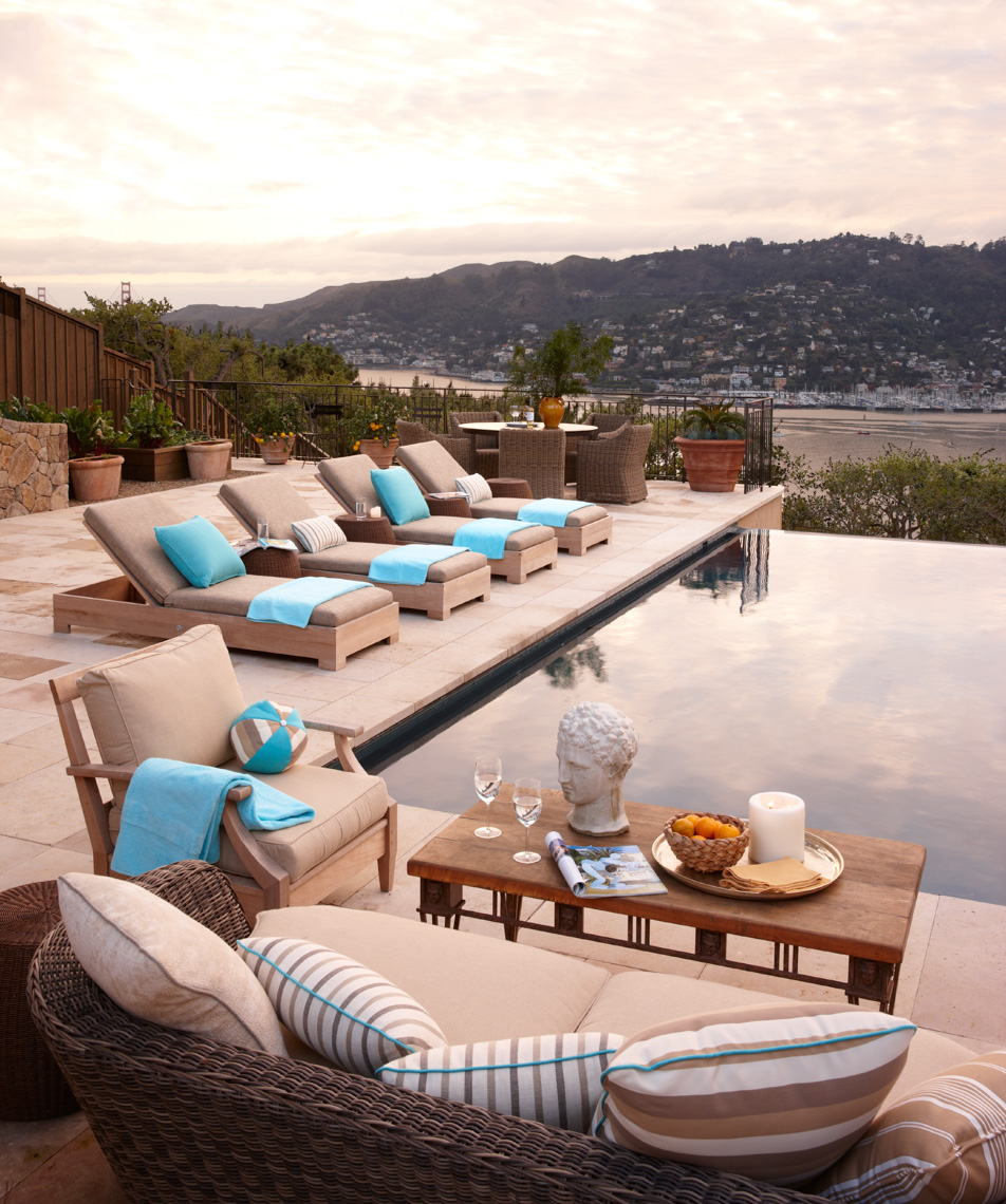 Outdoor teak furniture with cushions around pool patio with view at dusk