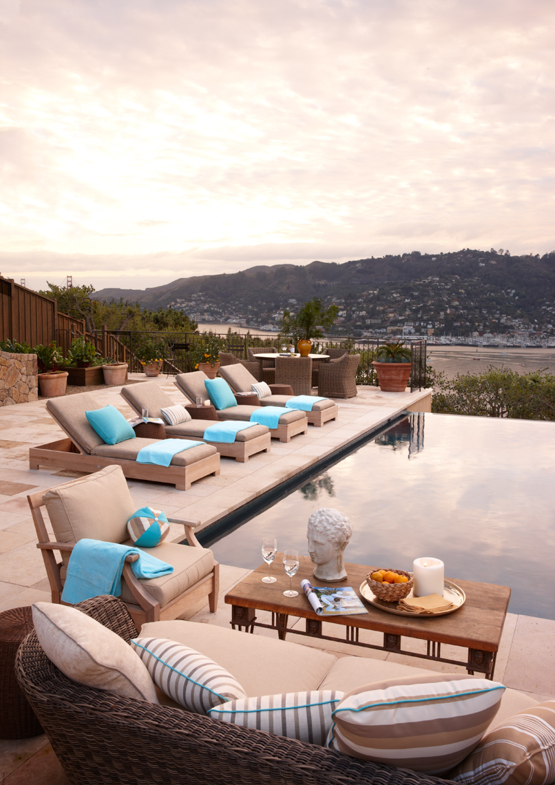 Wooden furniture with white cushions around pool patio