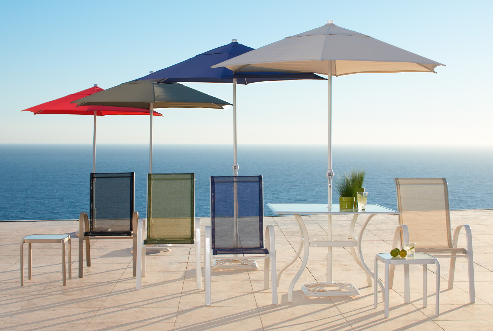 Modern chairs and umbrellas on outdoor patio near ocean