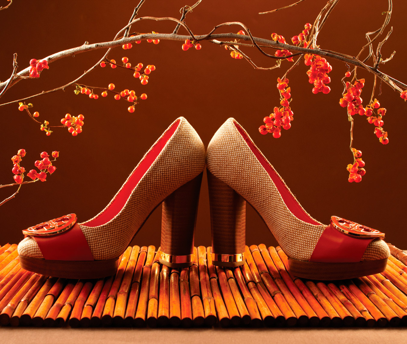 red and tan heels on wooden surface with holly branch above
