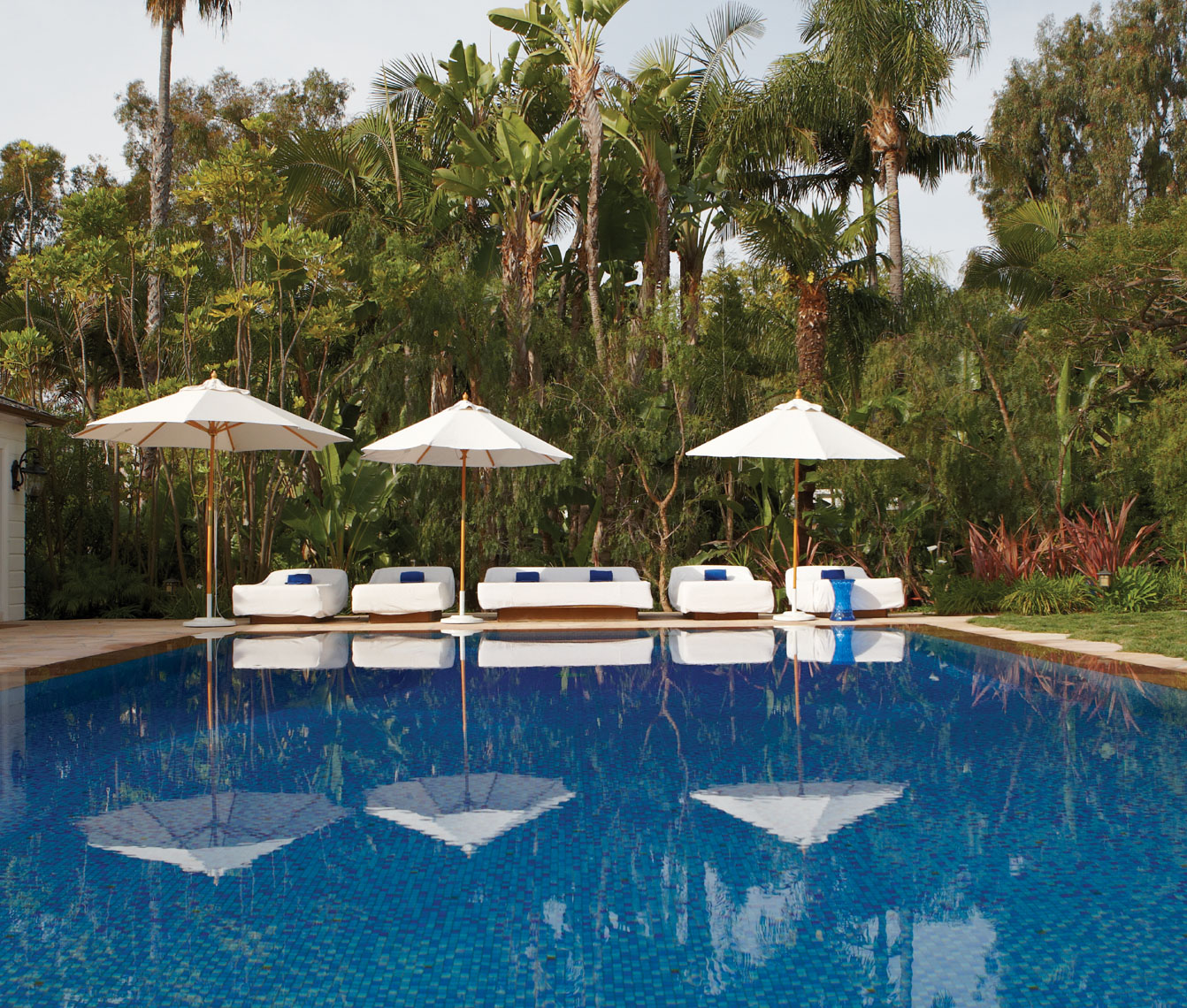Poolside outdoor furniture with white umbrellas and blue water