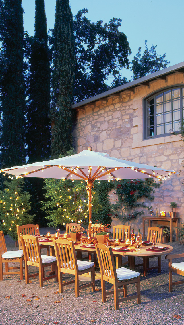 Teak dining table and chairs with umbrella at dusk San Francisco lifestyle photographer
