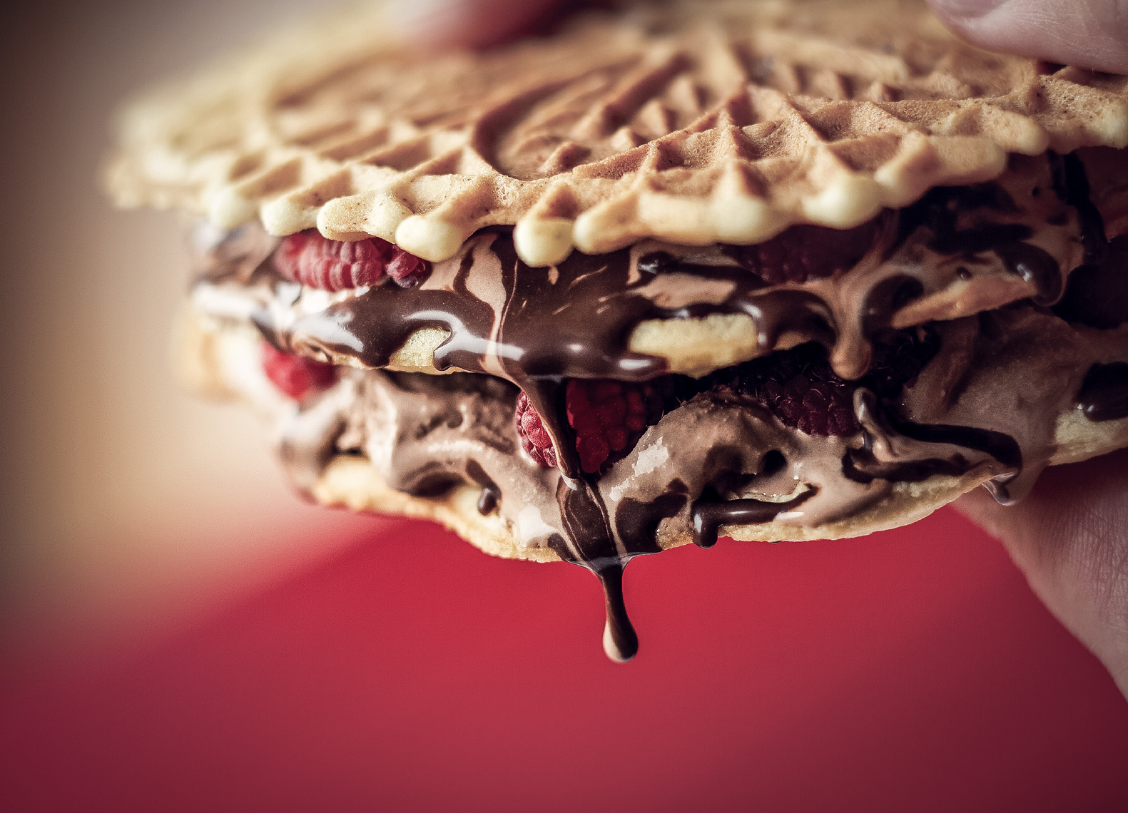 dripping chocolate waffle sandwich with raspberries