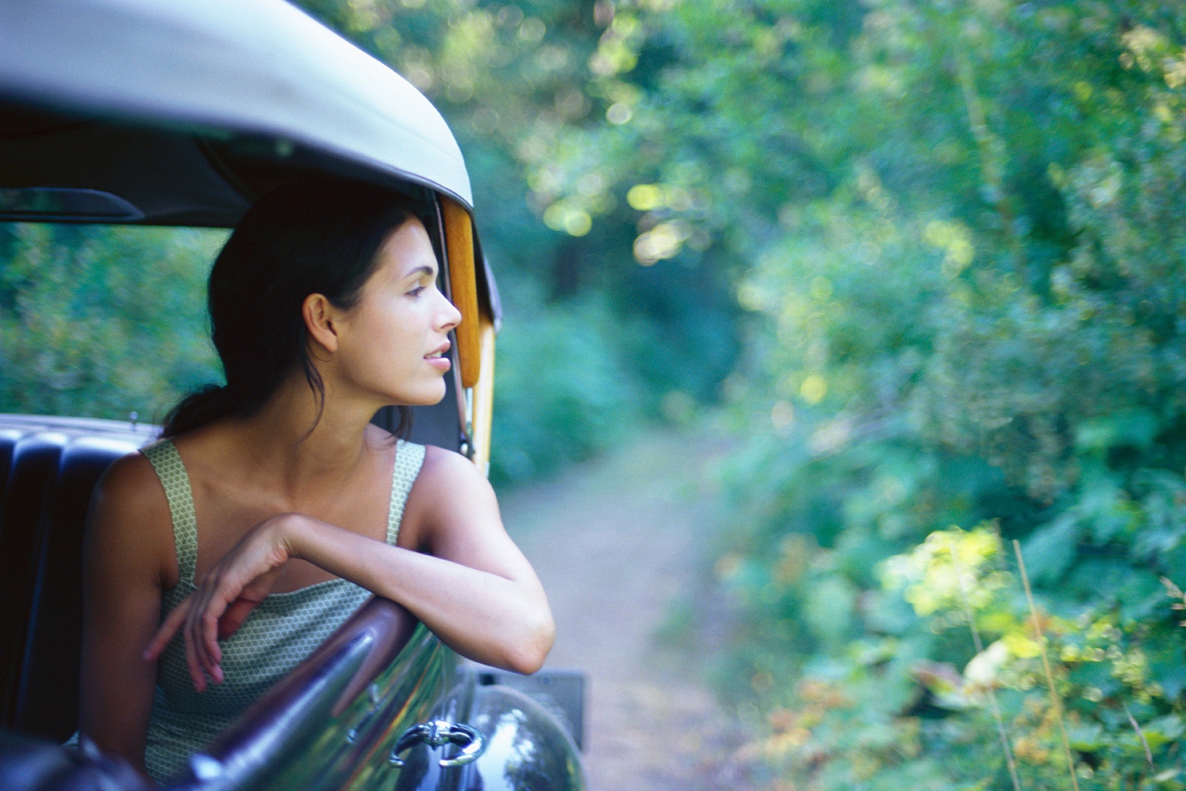 Woman in green dress looking out the window of and old Ford car on a country road