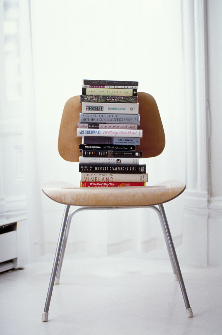 stack of books on Eames wooden school chair with metal legs