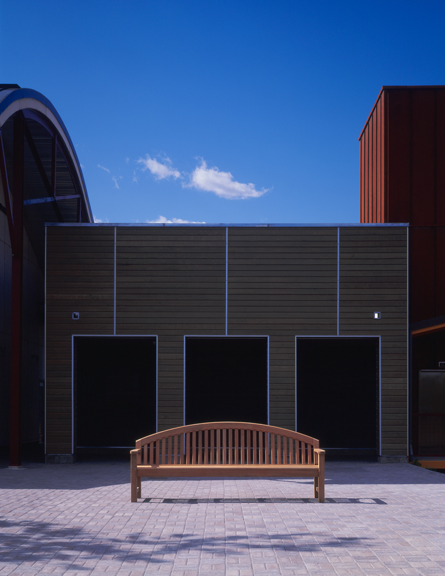 Teak bench in front of modern architectural building with blue sky
