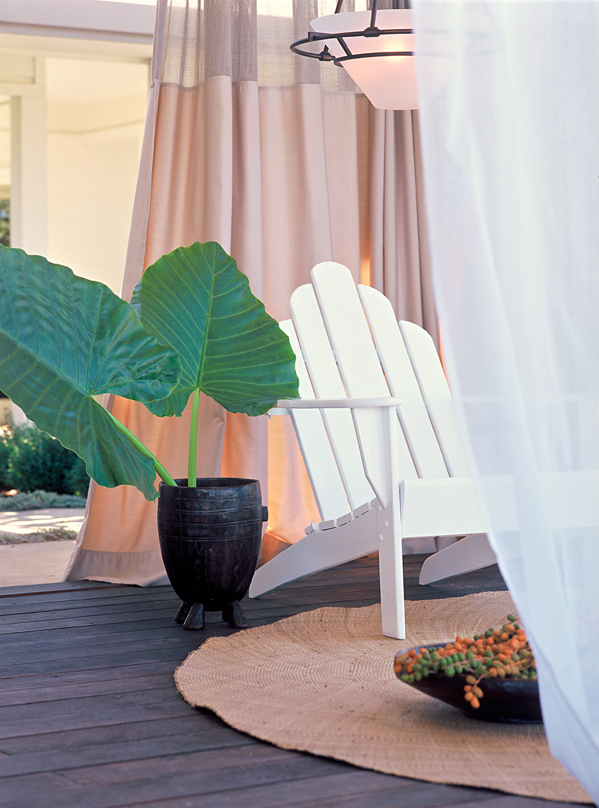 White adirondack chair and potted plant with large green leaves on jute rug